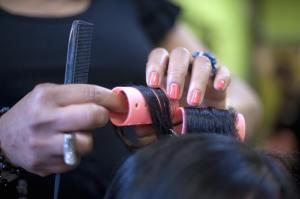 Hair Stylist Putting Rollers in Woman's Hair
