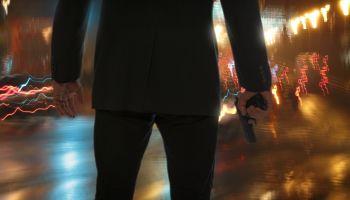 Bodyguard standing with gun during rain at night.
