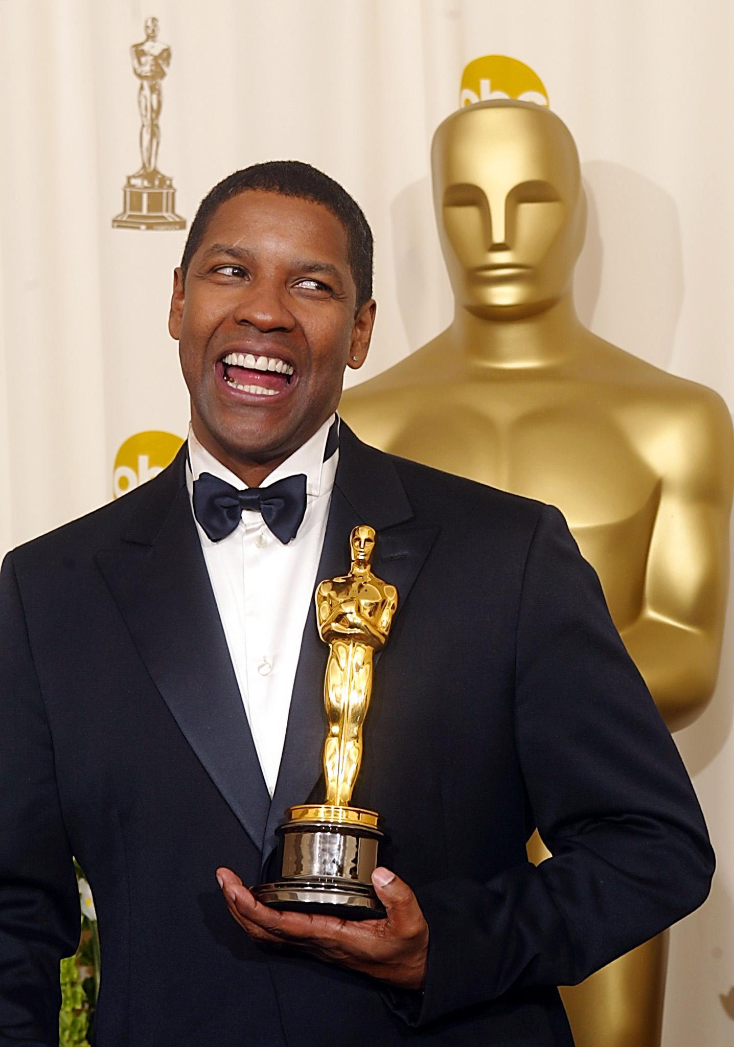 US actor Denzel Washington holds his Oscar after