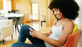 Mixed race woman using cell phone in armchair