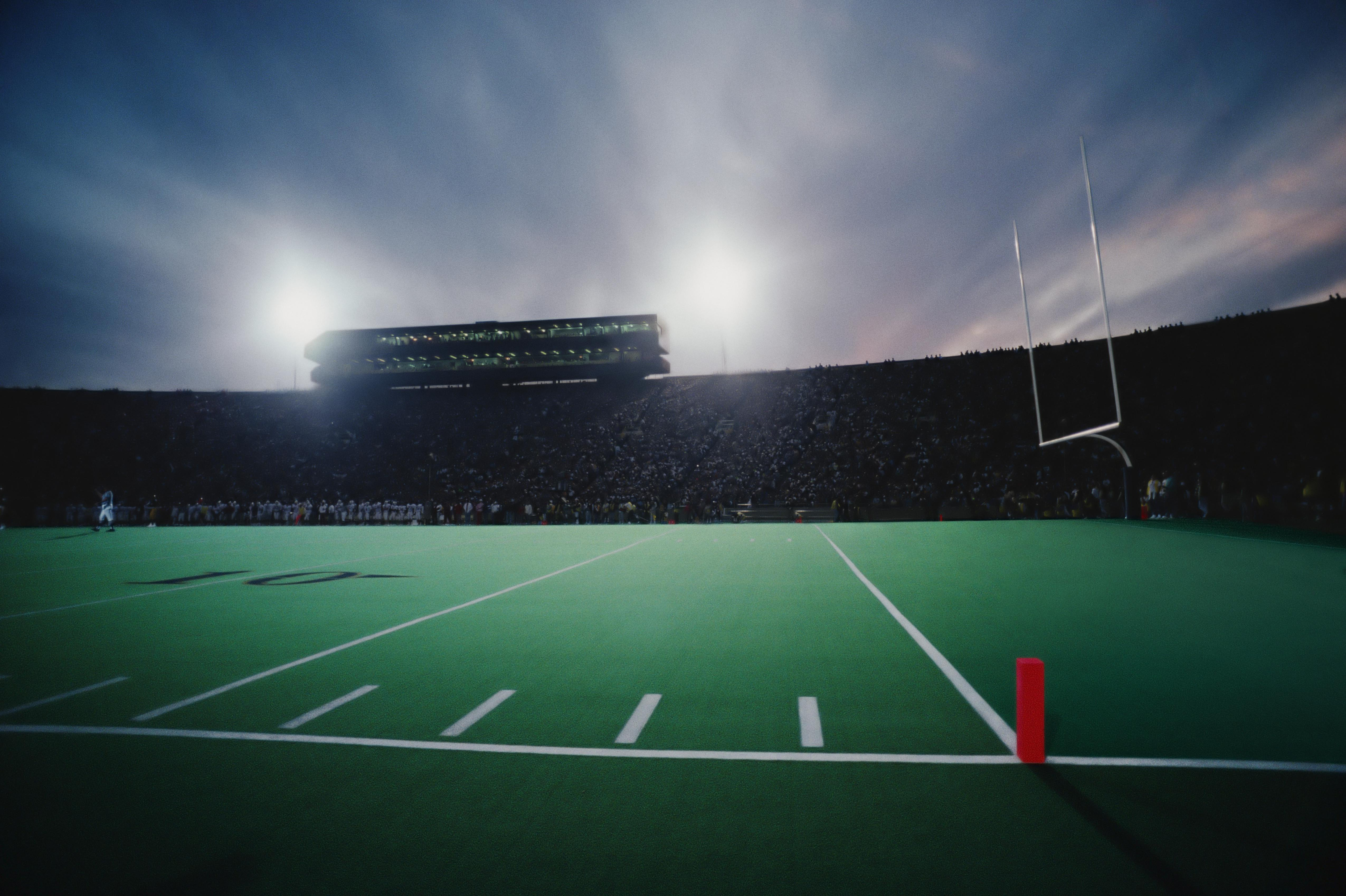 Football stadium filled with spectators during game, twilight