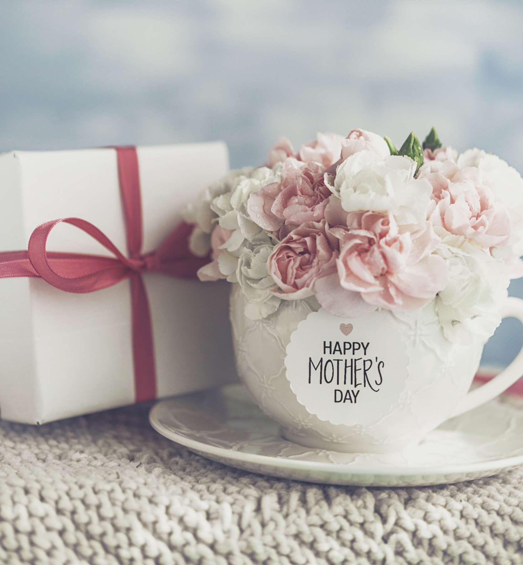 Mother's Day gift and cup filled with fresh carnation bouquet