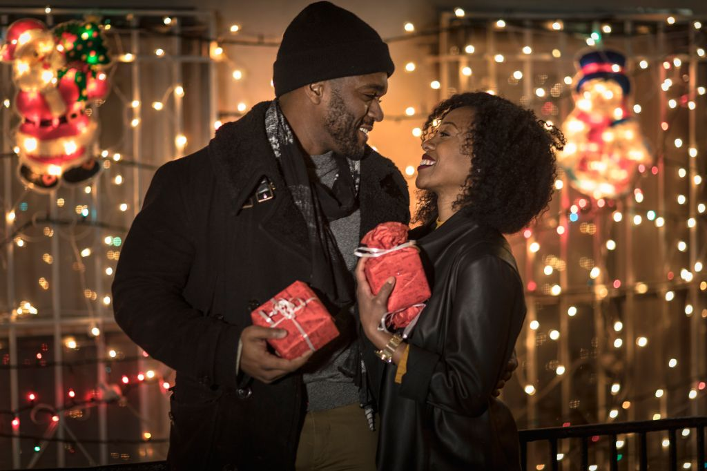 Romantic couple exchanging christmas gifts at night, New York, USA